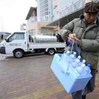 A man carries bottled water he got from a supply water tank in Chiba prefecture, near Tokyo, Japan, after the government issued a warning of elevated levels of radioactive iodine in tap water. (AP)