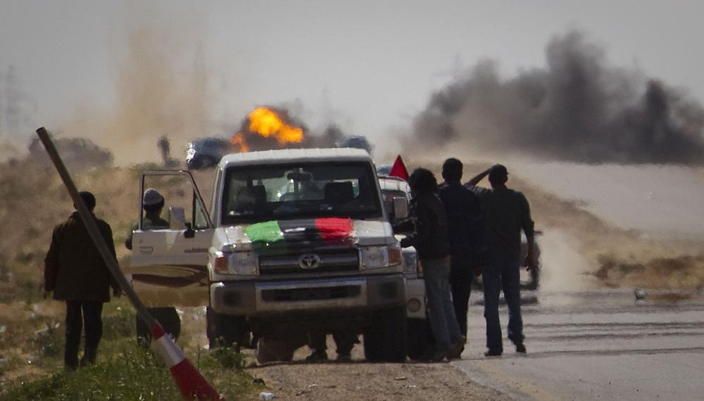 Libyan rebels stop on the road as mortars from Moammar Gadhafi's forces are fired on them on the outskirts of the city of Ajdabiya, south of Benghazi, eastern Libya Tuesday. (AP)