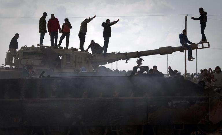 Libyan people celebrate on a tank belonging to the forces of Moammar Gadhafi in the outskirts of Benghazi, eastern Libya, Sunday. (AP /Anja Niedringhaus)