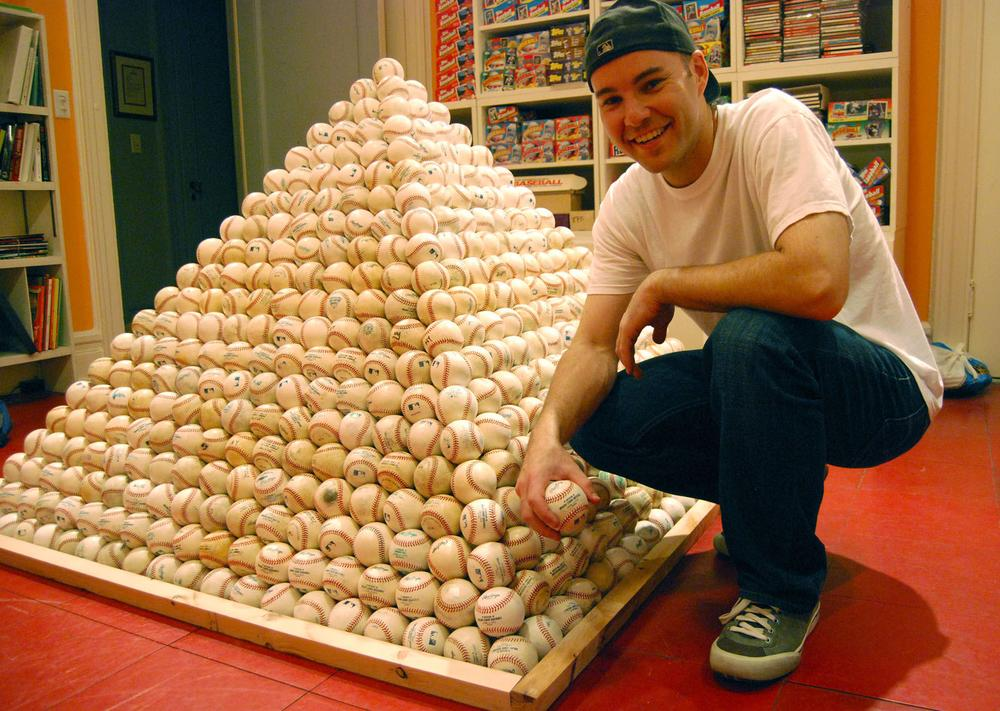 Baseball enthusiast Zack Hample and a pyramid of the baseballs he collects. (Anchor)
