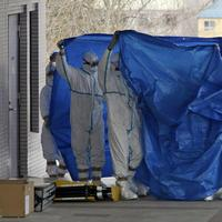 Japan's Self-Defense Force's members and others in protective gear hold blue sheets as they help to transfer workers who stepped into contaminated water on Thursday during their operation at the Fukushima Dai-ichi nuclear plant, at a hospital in Fukushima, northern Japan. (AP/Yomiuri Shimbun, Takuya Yoshino)