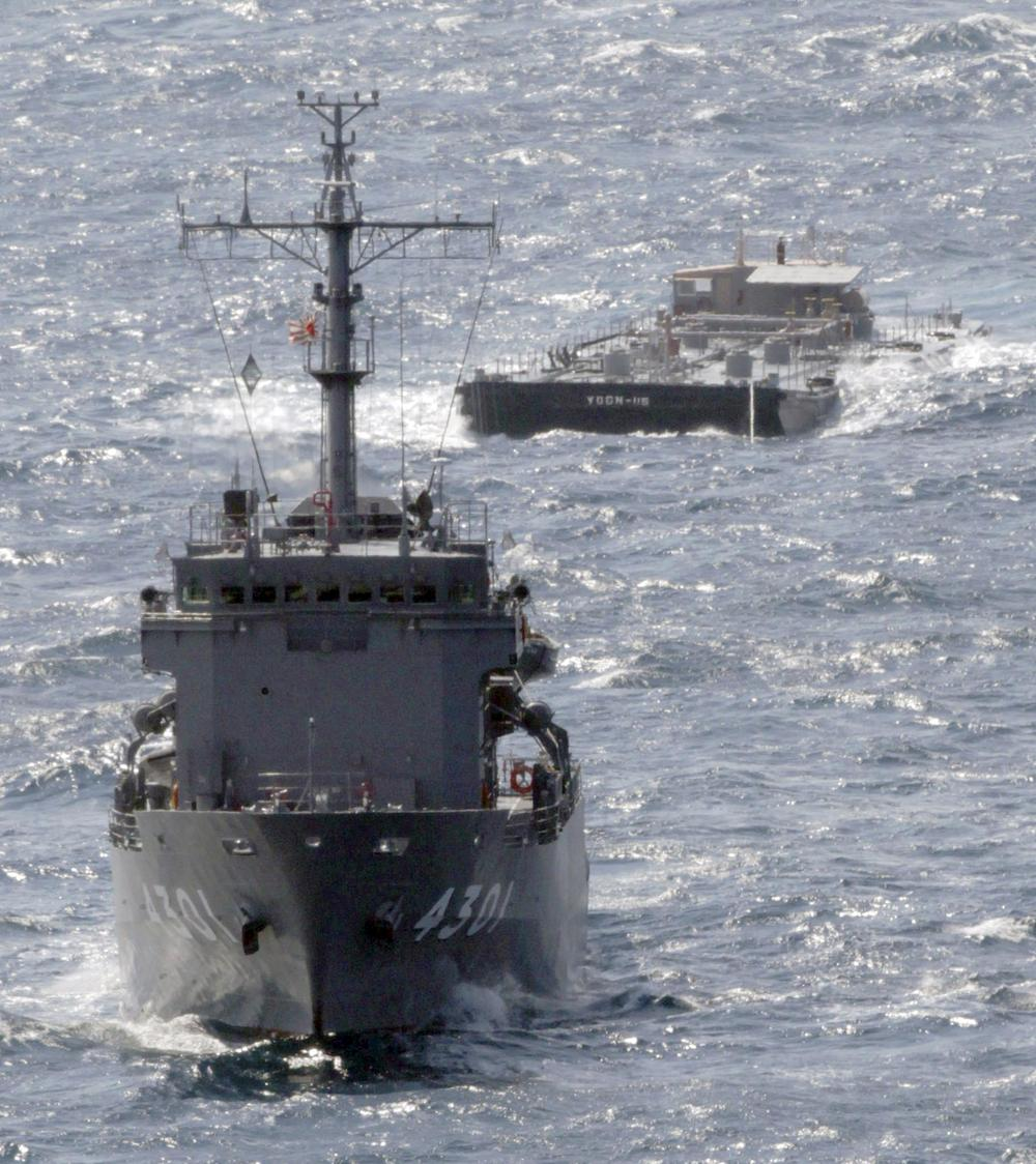 U.S. Navy's barge YOGN-115, back, is towed by Japan's Maritime Self-Defense Force's multi purpose support ship off the coast of Isumi, Japan, Saturday. (AP)