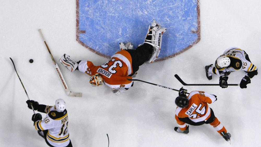 Philadelphia Flyers' Brian Boucher (33) throws his stick, trying to block a shot by Boston Bruins' Nathan Horton (18) as Matt Carle (25) and David Krejci (46), of Czech Republic, look on during the third period of the game on Sunday in Philadelphia. Boston won 2-1. (AP)