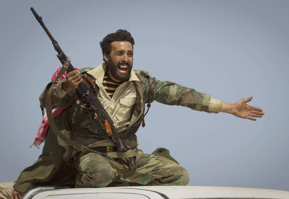 A Libyan rebel urges people to leave, as shelling from Moammar Gadhafi's forces started landing on the frontline outside of Bin Jawaad, 150 km east of Sirte, central Libya. (AP)