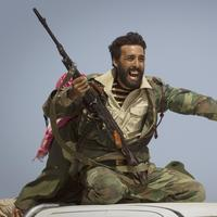 A Libyan rebel urges people to leave, as shelling from Gadhafi's forces started landing on the frontline outside of Bin Jawaad, 150 km east of Sirte, central Libya. (AP)