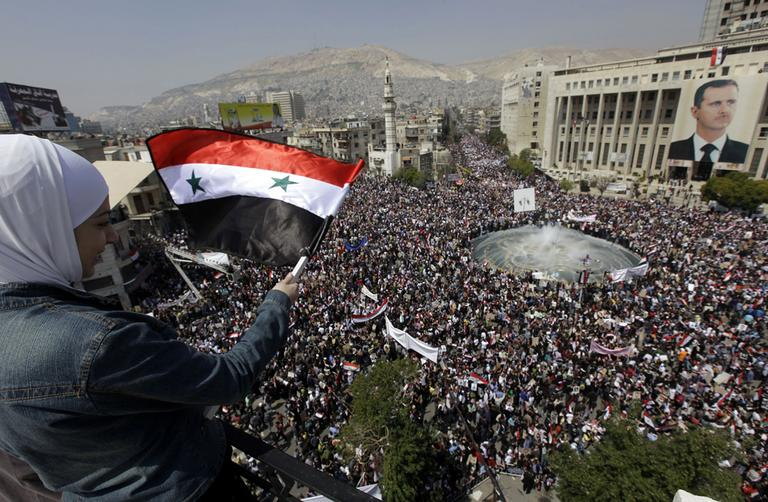 Amid the resignation of President Bashar Assad's cabinet, pro-government demonstrators gathered in Damascus, Syria, on Tuesday to show their support for Assad as he faces the biggest challenge to his 11-year rule. (AP)