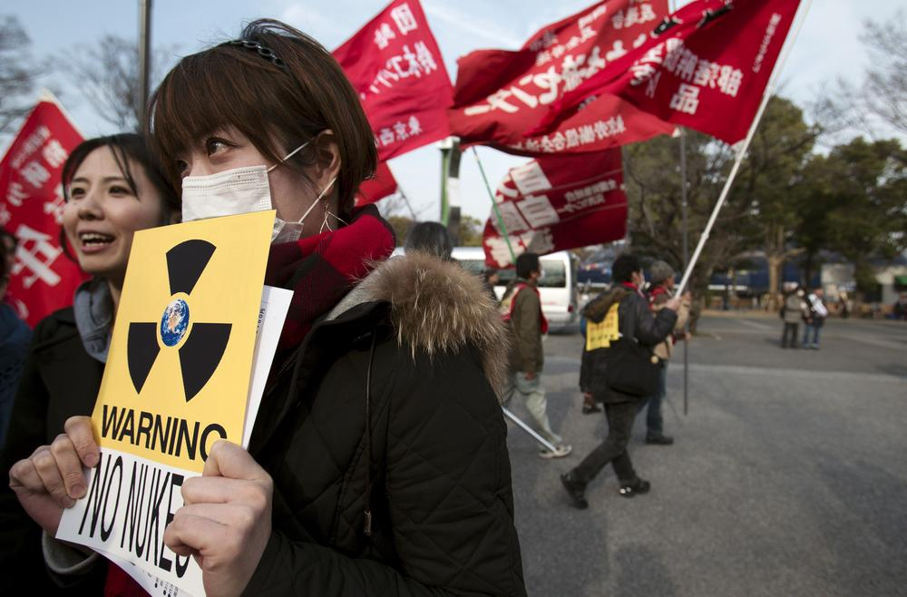 A woman holds a sign against nuclear power during anti-war and anti-nuclear march in Tokyo that have taken place since the earthquake. (AP)