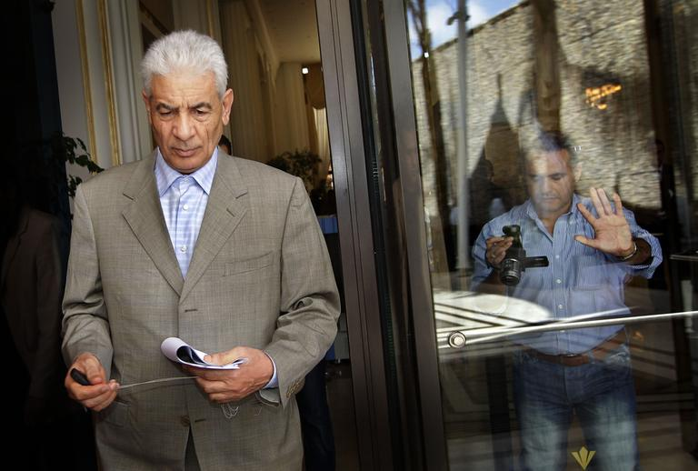 Libya's Foreign Minister Moussa Koussa leaves after reading a statement to journalists in Tripoli March 18. (AP)