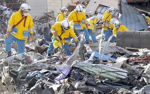 Police officers search for missing persons in the rubble in Kamaishi, northern Japan, on Monday. (AP)