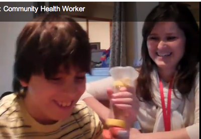 A health worker visits a young boy at home to remind him how to use his asthma medications
