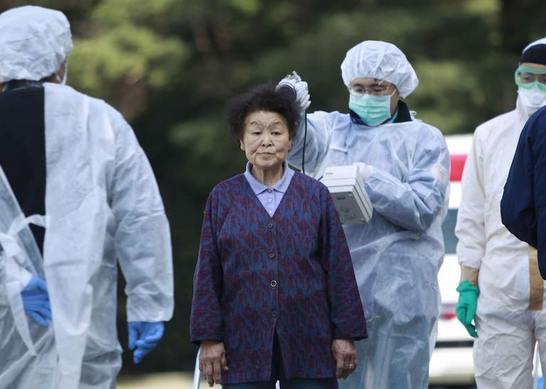 Residents evacuated from areas surrounding the Fukushima nuclear facilities damaged in Friday's massive earthquake, are checked for radiation contamination, Sunday, Japan. (AP/Wally Santana)
