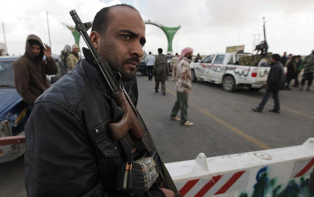 A Libyan rebel fighter guards the roadway to the western gate of Ajdabiya, Libya. (AP)