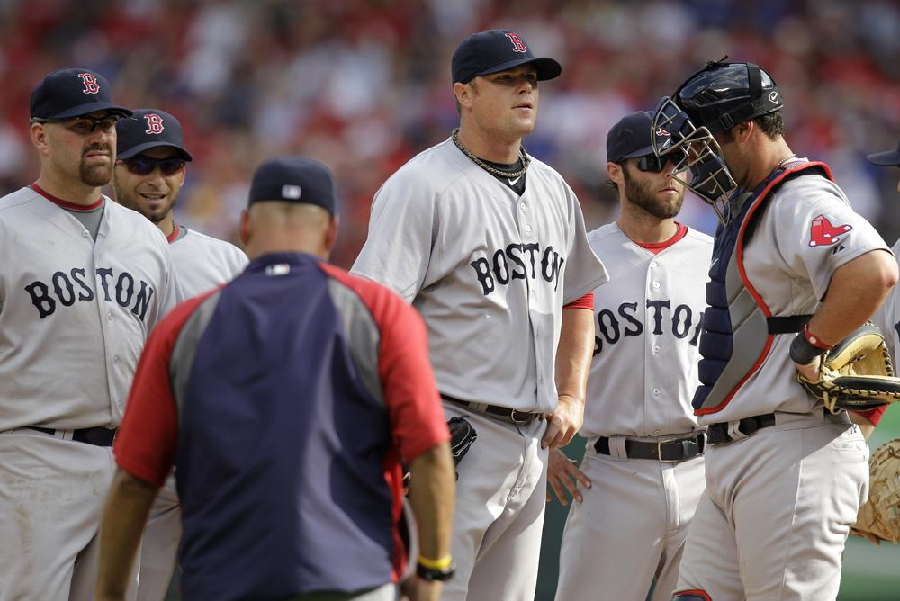 Boston Red Sox's Jon Lester, center, stands surrounded by teammates as he waits to be pulled by manager Terry Francona, left front, in the sixth inning Friday in Texas. (AP)