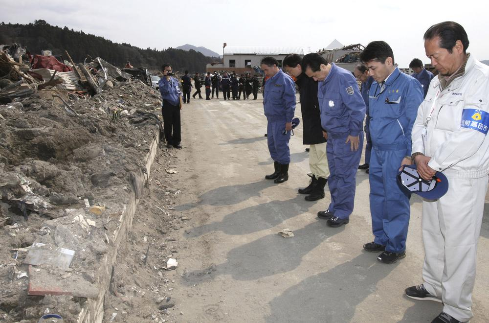 In this photo released by Prime Minister's Official Residence, Japanese Prime Minister Naoto Kan, third right, dressed in the blue work clothes, observes a minute of silence as he inspects the damage in the March 11 earthquake and tsunami devastated city of Rikuzentakata, Iwate Prefecture, northern Japan Saturday. (AP)
