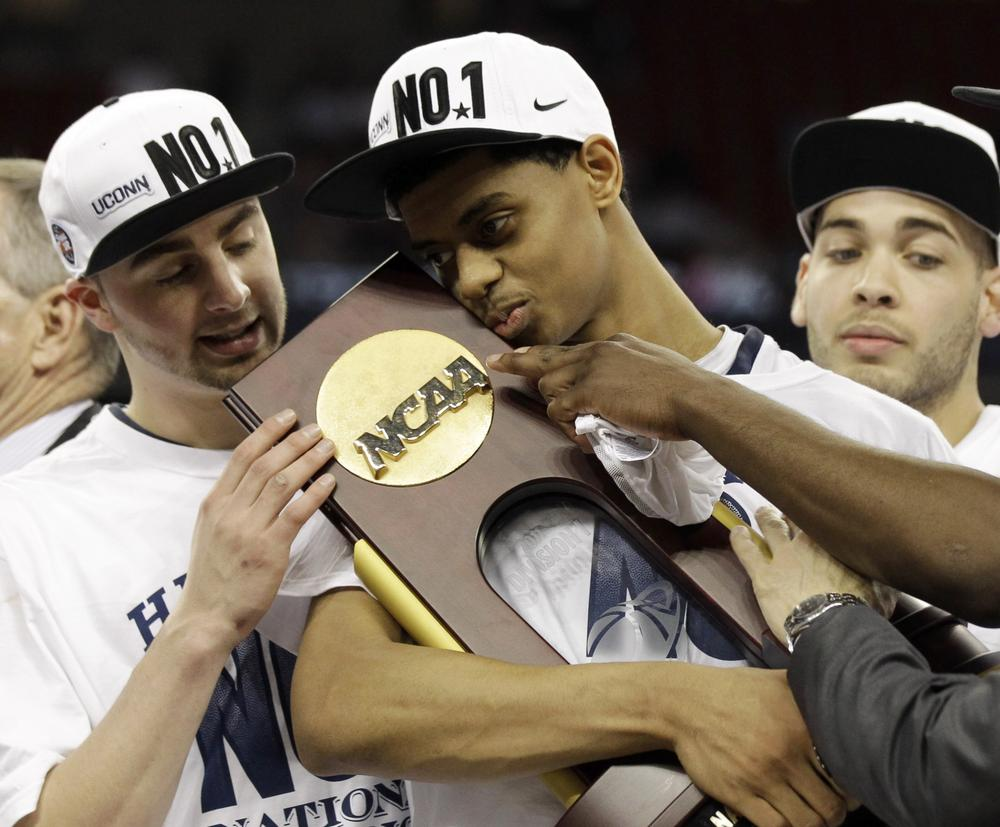 Connecticut's Jeremy Lamb, center, cradles the trophy after the men's NCAA Final Four college basketball championship game against Butler on Monday in Houston. (AP)