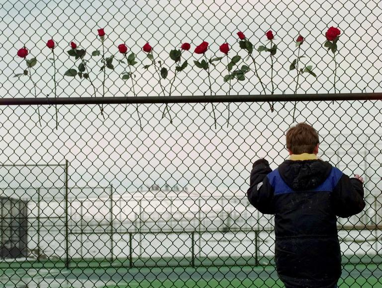 A boy looks past a make-shift memorial to the 13 killed in the Columbine High School massacre at the high school. (AP)