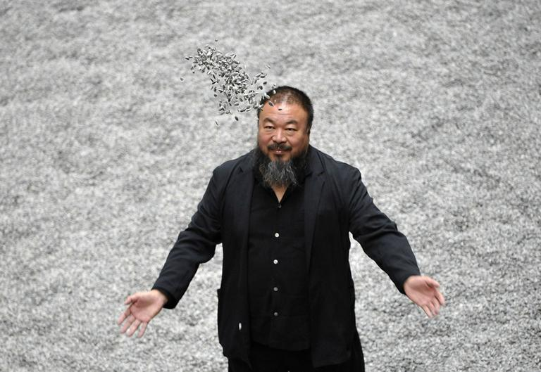 Chinese artist Ai Weiwei poses with some seeds from his art installation 'Sunflower Seeds' in London in 2010. (AP)
