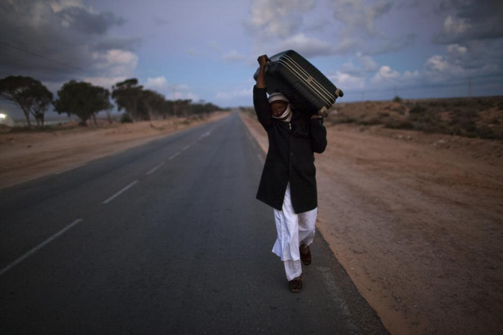 A man from Ghana, who used to work in Libya and fled the unrest in the country, carries his belongings as he arrive in a refugee camp after crossing from Libya at the Tunisia-Libyan border, in Ras Ajdir, Tunisia.  (AP)