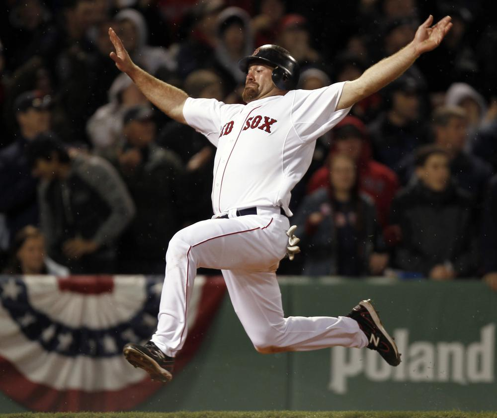 Boston's Kevin Youkilis goes flying into home to score on a double by teammate David Ortiz during the eighth inning of their 4-0 win over New York in the game at Fenway Park in Boston on Sunday. (AP)