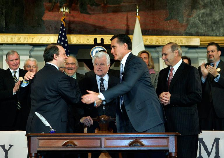 After signing Massachusetts' universal health care coverage law on April 12, 2006, then-Gov. Mitt Romney shakes hands with state Health and Human Services Secretary Timothy Murphy as Sen. Edward Kennedy and others look on at Faneuil Hall in Boston. (AP)