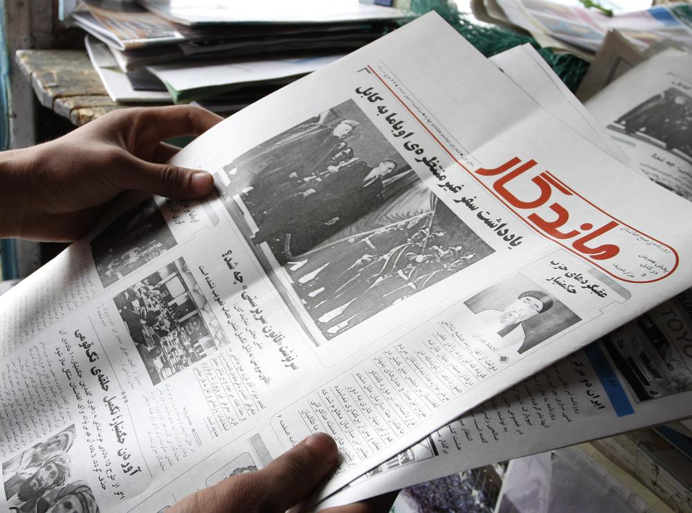 A man, unseen, reads an Afghan newspaper at a newsstand in Kabul, Afghanistan. (AP)