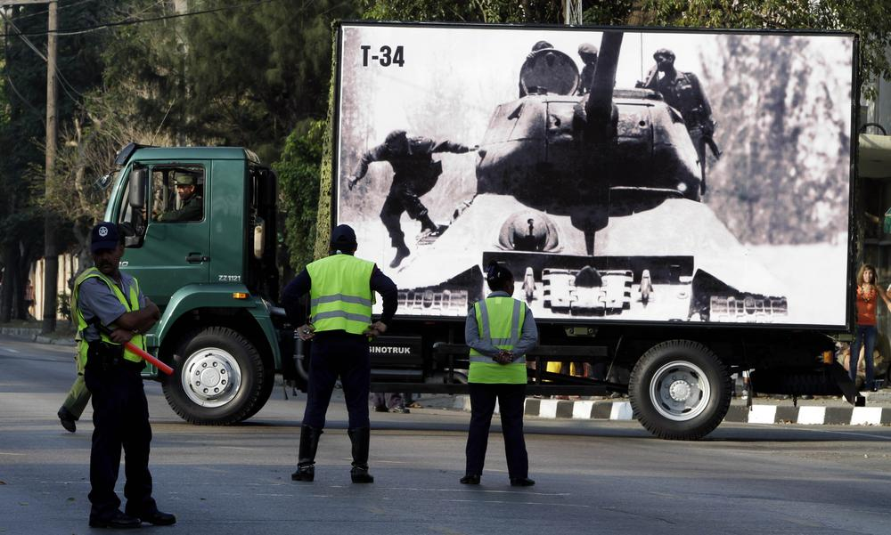 Police watch a truck carrying an April 1961 photograph of Cuba's leader Fidel Castro jumping from a tank, left, near the Bay Of Pigs, during rehearsals for an upcoming parade commemorating the 50th anniversary of the Bay of Pigs in Havana, Cuba. (AP)