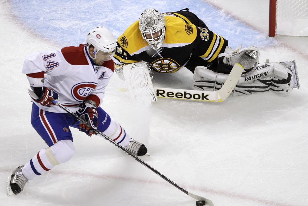 Boston Bruins goalie Tim Thomas, top, drops to the ice to make a save on a shot by Montreal Canadiens center Tomas Plekanec during the playoff game in Boston on Thursday. (AP)