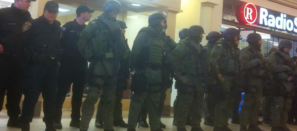 In this cell phone image, SWAT team members and local police line up in the Burlington Mall as it's searched. (Courtesy)