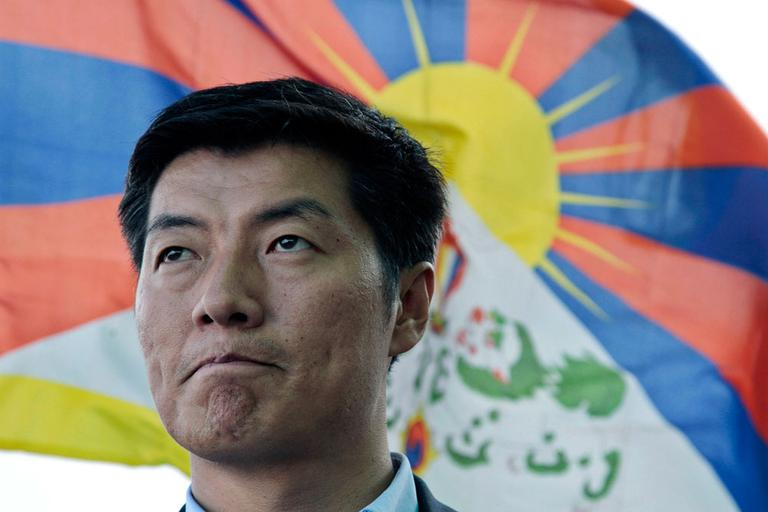 Lobsang Sangay talks in front of a Tibetan flag in Dharamsala, India, on March 20. (AP)