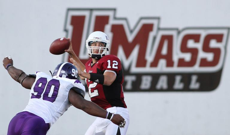 Massachusetts quarterback Kyle Havens looks to pass as Holy Cross defender Mude Ohimor closes in during an NCAA college football game in Amherst, Mass. in September. (AP)