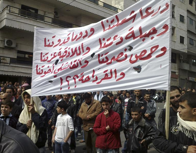 In this citizen journalism image made on a mobile phone and acquired by the AP, Syrian anti-government protesters carry a banner in the coastal city of Banias, Syria, Friday. (AP)