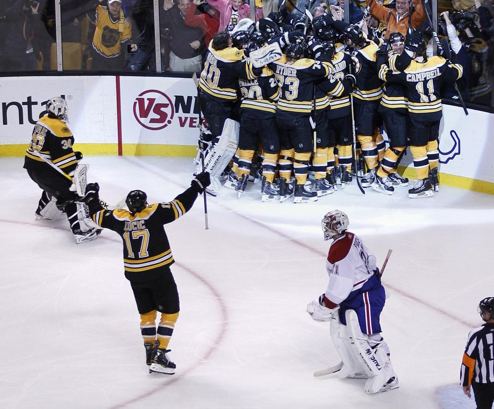 Canadiens goalie Carey Price, bottom right, skates off the ice as the Boston Bruins surround Nathan Horton after he scored the game-winning goal during the second overtime period in Game 5 in Boston, Saturday.  (AP)
