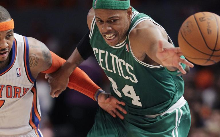 Celtics captain Paul Pierce lunges for the ball ahead of Knicks forward Carmelo Anthony during their playoff game Sunday in New York. (AP)
