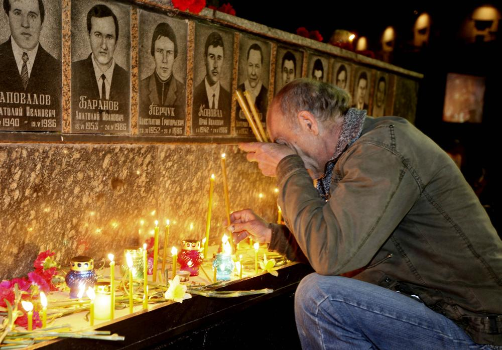 A Ukrainian lights candles to commemorate those who died after the Chernobyl nuclear disaster in Slavutich on Tuesday. (AP)
