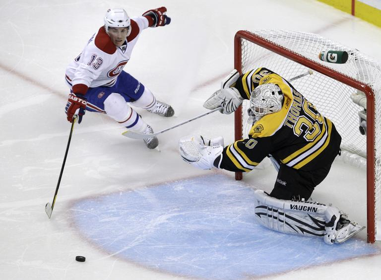 Bruins goalie Tim Thomas clears the puck away after a save as Montreal Canadiens left wing Michael Cammalleri tries to gain possession. (AP)