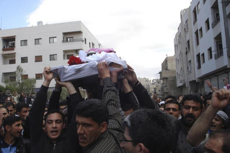 In this citizen journalism image made on a mobile phone, Syrian anti-government protesters carry the coffin of an activist who was killed in Quaboun near Damascus, Syria, April 23. (AP)
