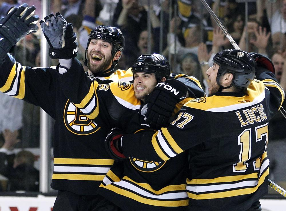 Zdeno Chara, left, and Milan Lucic, right, celebrate with Nathan Horton after he scored the game-winning goal against the Montreal Canadiens in Game 7 Wednesday.  (AP)