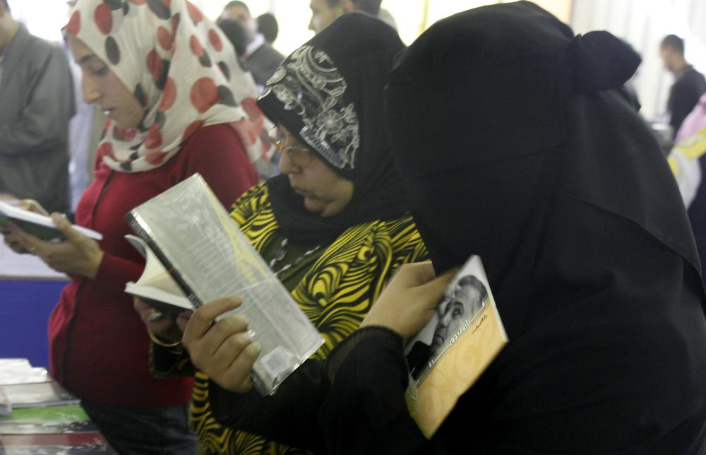 Egyptians review Arabic novels and poetry at the Cairo Book fair in Egypt in 2010. (AP)