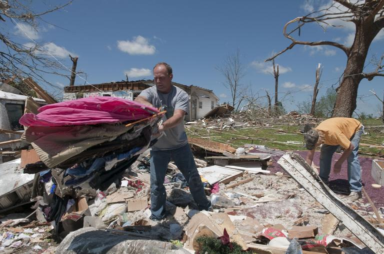 Mark Plunkett, left, with the help of Allen Southerland, right, find some of his wife's clothing in the debris of his Phil Campbell, Ala., home Thursday. (AP)