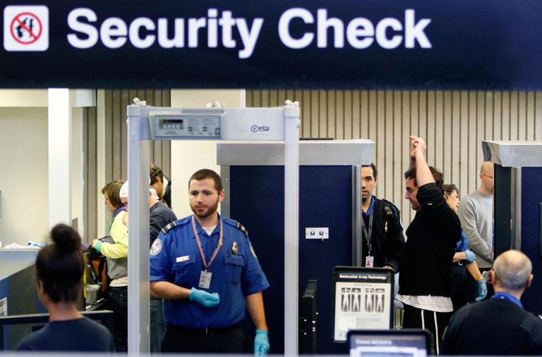 Passengers pass through security, including a full-body scanner, at Logan International Airport on Nov. 24, 2010. (AP)