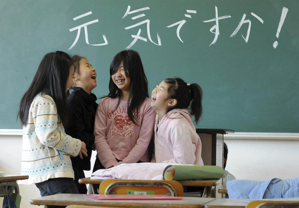 """Elementary school children share a chuckle as they reunite for the first time since the March 11 earthquake at Masuda Nishi elementary school in Natori, Miyagi Prefecture, northern Japan. The words on the blackboard read """"How have you been doing?"""" (AP)"""