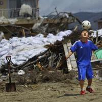 A child plays with a soccer ball in Ishinomaki, Miyagi Prefecture, northeastern Japan. (AP)