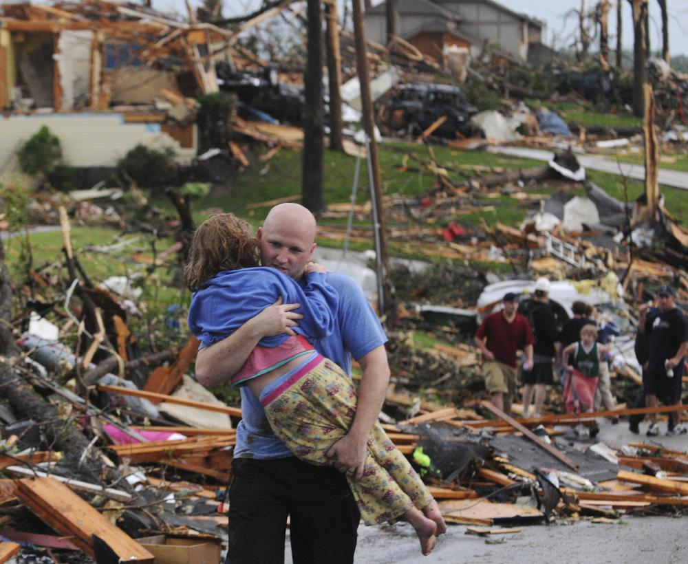 A man carries a young girl who was rescued after being trapped with her mother in their home after a tornado hit Joplin, Mo. on Sunday evening, May 22, 2011. (AP)