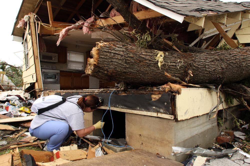 Nurse Danielle Sipi of Jefferson City, Mo., shines a flashlight into the crawlspace of a home in Duquesne, Mo, right outside of Joplin. (AP)