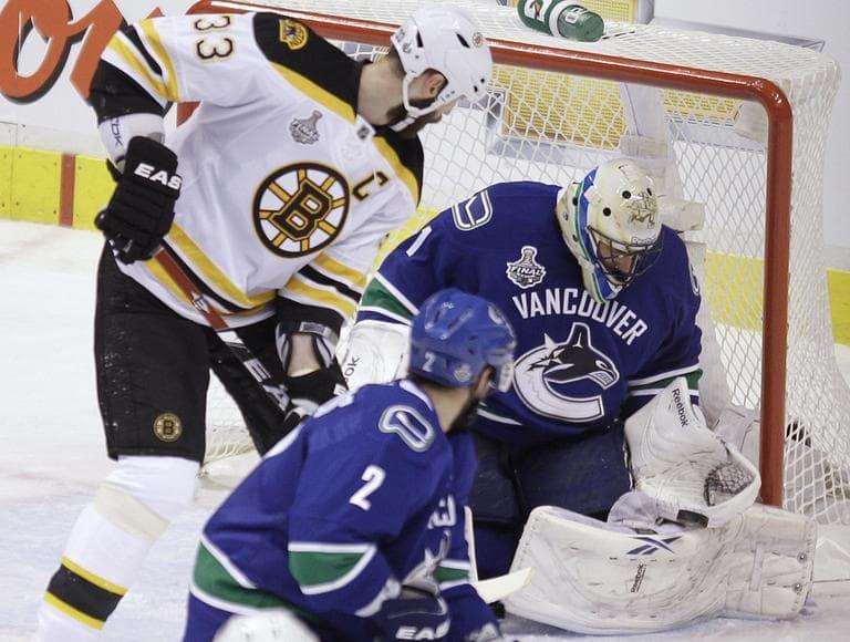 Vancouver Canucks goalie Roberto Luongo makes a save as Bruins defenseman Zdeno Chara and Canucks defenseman Dan Hamhuis (2) look for the rebound during Game 1 Wednesday, in Vancouver, British Columbia. (AP)