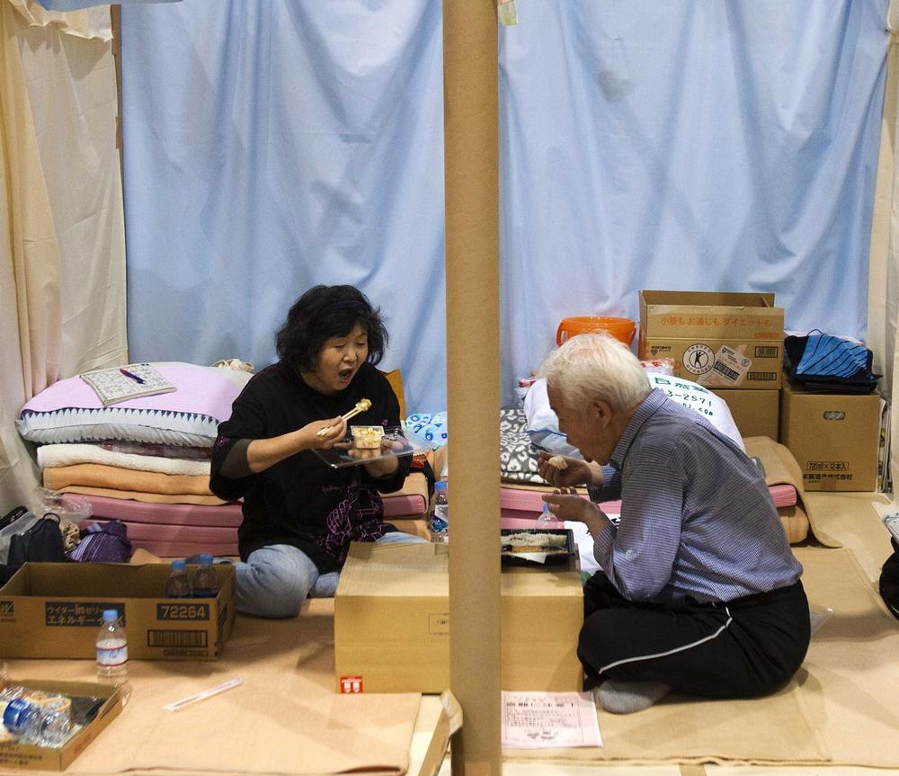 A Japanese refugee couple eat their dinner in their allotted space at an arena used as evacuation center in Koriyama, Fukushima prefecture, northeastern Japan in late May. (AP)