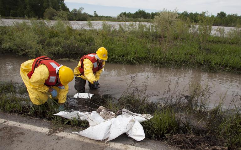 Clean up crews work to collect oil from along side the Yellowstone River in Laurel, Montana, Monday July 4, 2011. (AP)
