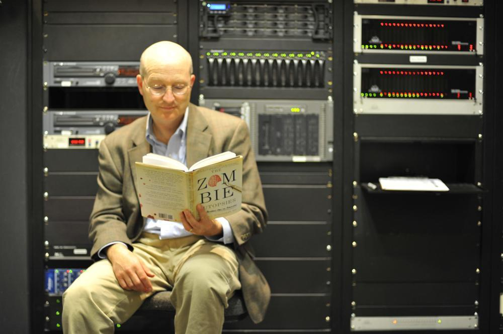 """Steven Schlozman, author of """"The Zombie Autopsies,"""" reads up on his new book, before heading into the """"On Point"""" studio at WBUR. (Alex Kingsbury/WBUR)"""
