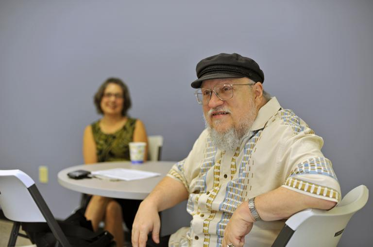 George R. R. Martin chats with employees from WBUR in the staff kitchen before heading into the studio and talking with Tom Ashbrook. (Alex Kingsbury / WBUR)