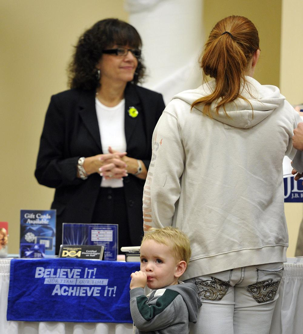 Xander Lee, 2, waits with his mother Amanda Lee as she searches for employment opportunities during a jobs fair in Rockford, Ill. (AP)